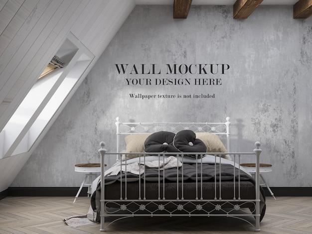 屋根裏部屋の寝室の壁紙のモックアップ、インテリアに金属製のベッド