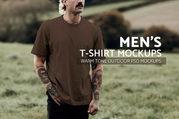 Attractive man in brown t-shirt with design space standing in countryside
