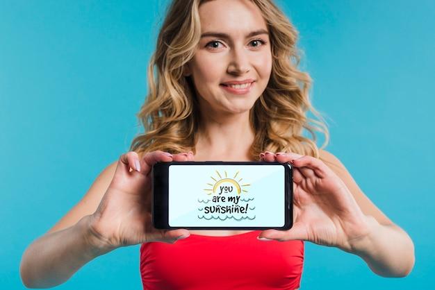 スマートフォンのモックアップを提示する魅力的な女性