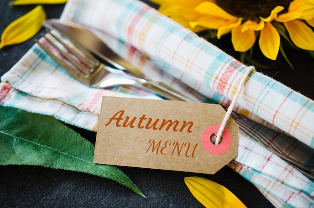 Autumn table place setting with empty tag, cutlery with napkin and sunflower.