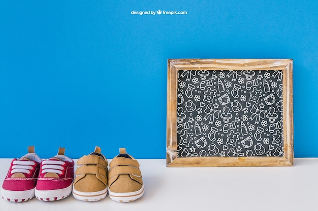 Baby mockup with slate and two pairs of shoes