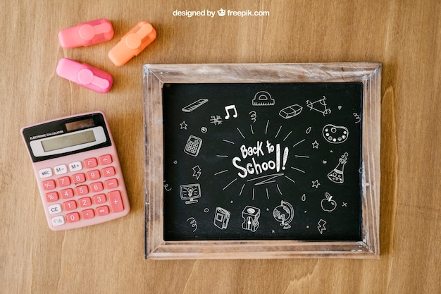 Back to school composition with slate and calculator on wooden surface