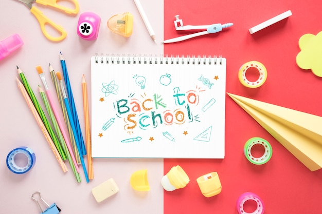Back to school supplies on pink and red background