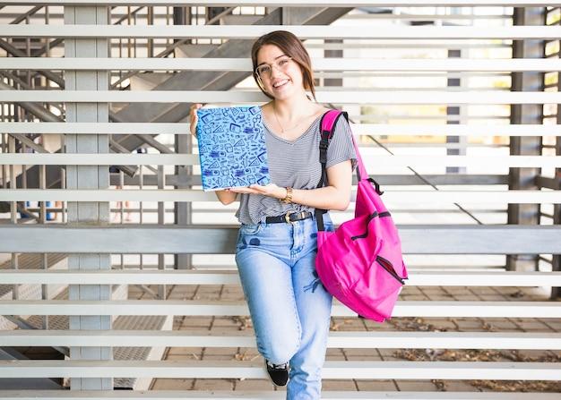 책 표지를 제시하는 여자와 함께 학교 개념으로 돌아 가기