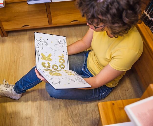Вернуться в школу концепции с книгой чтения девочки в библиотеке