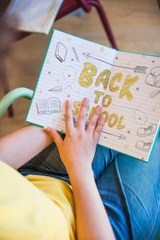 도서관에서 소녀 낭독 서와 함께 학교 개념으로 돌아 가기