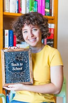 슬레이트를 보여주는 여자와 학교 개념으로 돌아 가기