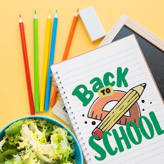 노트북 및 샐러드와 함께 학교 모형으로 돌아 가기