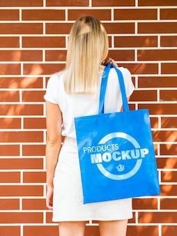 Back view woman holding a plain blue bag