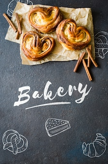 Запеченные свежие ароматные булочки с корицей. традиционная домашняя выпечка на темном фоне.