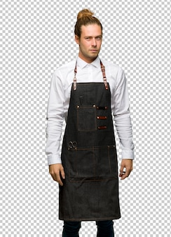 Barber man in an apron feeling upset