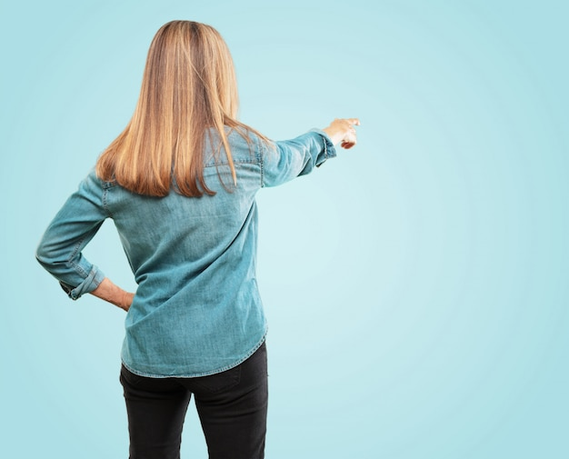 Beautiful senior woman back view, hand on hip, pointing with other hand to an object in the distance