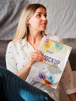 Beautiful woman holding a mock up magazine