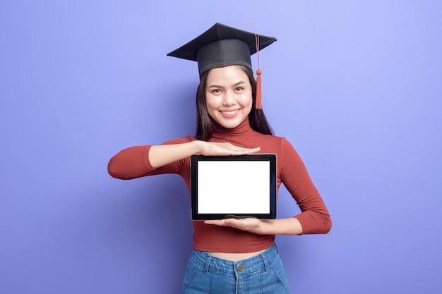 卒業の帽子で美しい女性はタブレットのモックアップを保持しています。