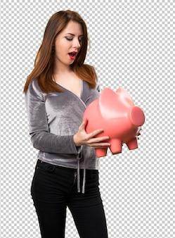 Красивая молодая девушка держит копилку