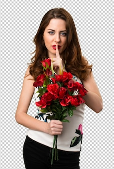 Beautiful young girl holding flowers making silence gesture