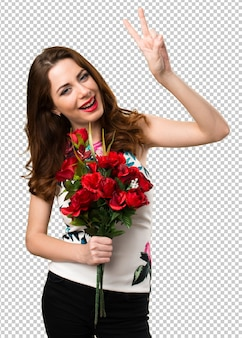 Beautiful young girl holding flowers making victory gesture