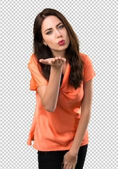 Beautiful young girl sending a kiss
