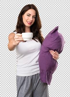 一杯のコーヒーを保持している枕を持つ美しい少女