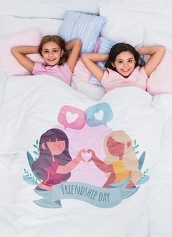 Best friends relaxing in bed with cute blanket mock-up