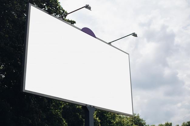 여러 가지 색상의 광고와 조명이있는 bilbard는 일광에서 거리에 서 있습니다. 아래 사진
