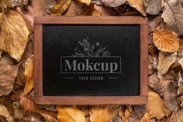 Mockup di lavagna nera su foglie d'autunno