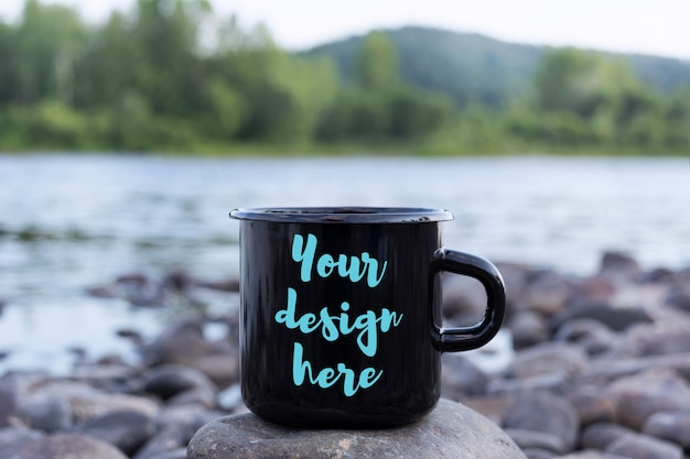 Black campfire mug mockup with stony river bank