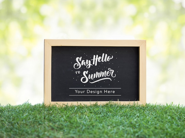 Black chalkboard on green grass mockup