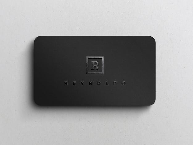 黒のビジネスカードのモックアップに黒のエンボスロゴ
