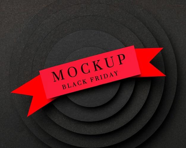 生地のレイヤーに黒い金曜日のモックアップ赤いリボン