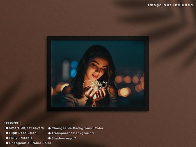 그림자가 있는 벽 배경에 매달려 있는 검은색 가로 사진 프레임 모형.