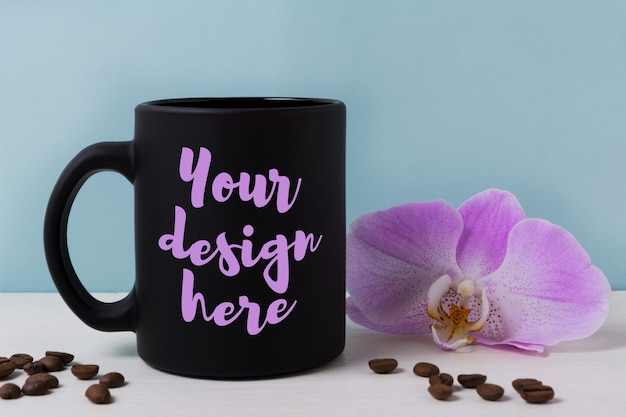 Black mug mockup with orchid and coffee beans