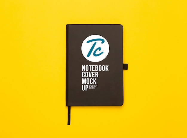 Black notebook coveron yellow background. mockup template for your design