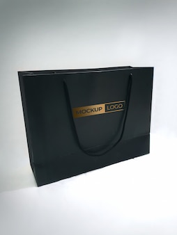 Black shopping paper bag mockup with golden logo