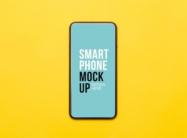 黄色の画面に黒いスマートフォン。あなたのデザインのモックアップテンプレート