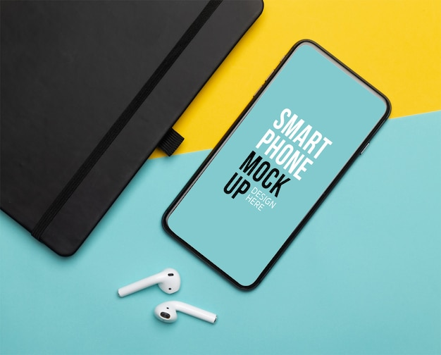 Black smartphone with screen and wireless earphones and notebook