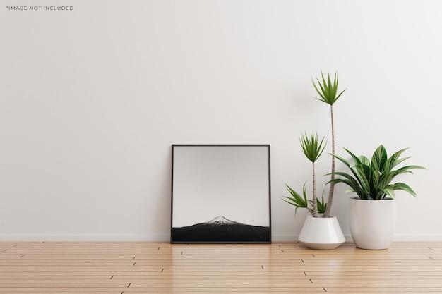 나무 바닥에 식물이 있는 흰색 벽 빈 방에 검정 사각형 사진 프레임 모형