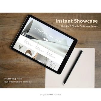 Black tablet on wooden desk mock up