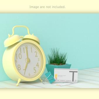 Blank business card beside clock on work desk