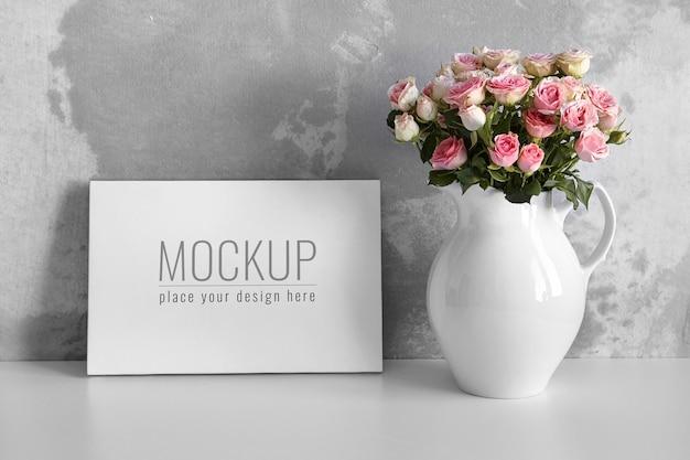 Макет пустого холста на белом столе с розовыми цветами в вазе на фоне бетонной стены