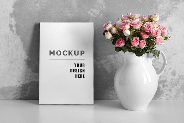 Макет пустого холста на белом столе с розовыми цветами в вазе на сером фоне стены