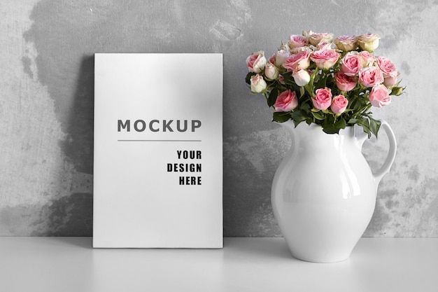 Blank canvas mockup on white table with pink flowers in vase on grey wall background