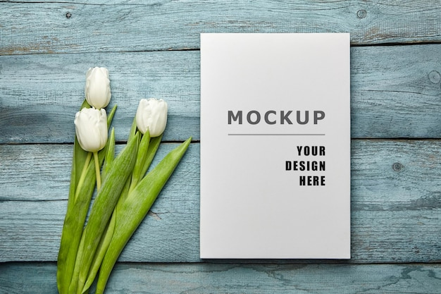 Blank canvas mockup and white tulip flowers on old light blue wooden surface flat lay