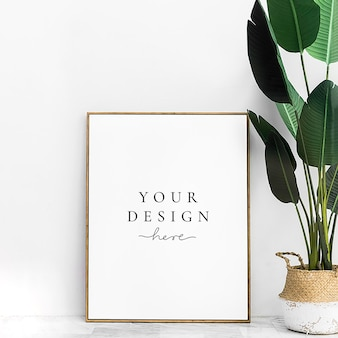 Blank gold photo frame by the houseplant on a floor