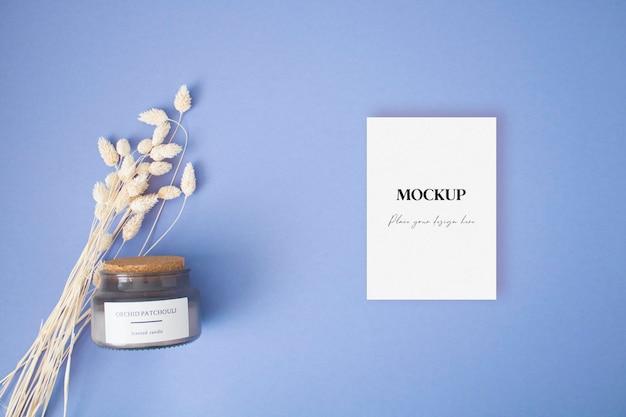 파란색 배경에 마른 풀과 촛불이 있는 빈 인사말 카드