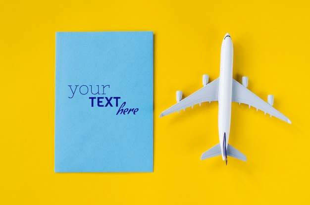 Blank greeting card mockup with airplane toy. summer travel concept.
