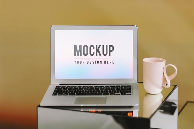 Пустой экран для ноутбука и розовая кофейная чашка