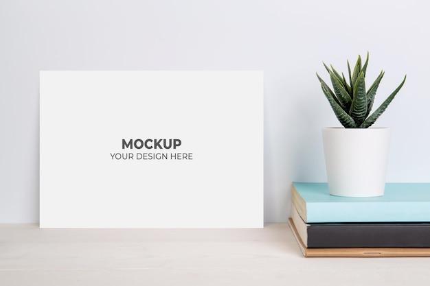 木製のテーブルの上の本に鉢植えの空白のモックアップ紙シートと植物