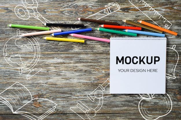 空白のノートブックと木製のテーブルにカラフルな鉛筆のセット。用紙の背景。モックアップ。バナー。上からの眺め