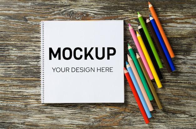 空白のノートブックと木製のテーブルにカラフルな鉛筆のセット。用紙の背景。モックアップ。上からの眺め